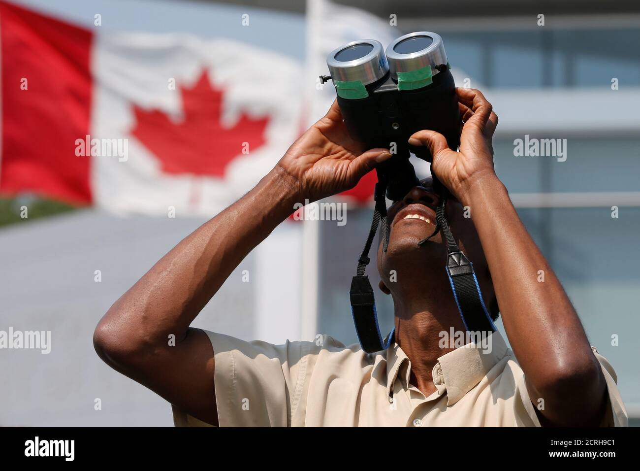 A man uses binoculars to watch a partial solar eclipse at the Canada Aviation and Space Museum in Ottawa, Ontario, Canada, August 21, 2017. REUTERS/Chris Wattie Stock Photo