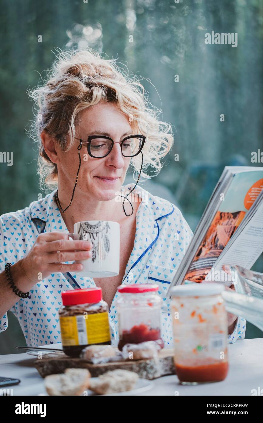 Blonde young mature woman with glasses in pyjamas at home in breakfast time, reading a magazine and having a cup of coffee Stock Photo