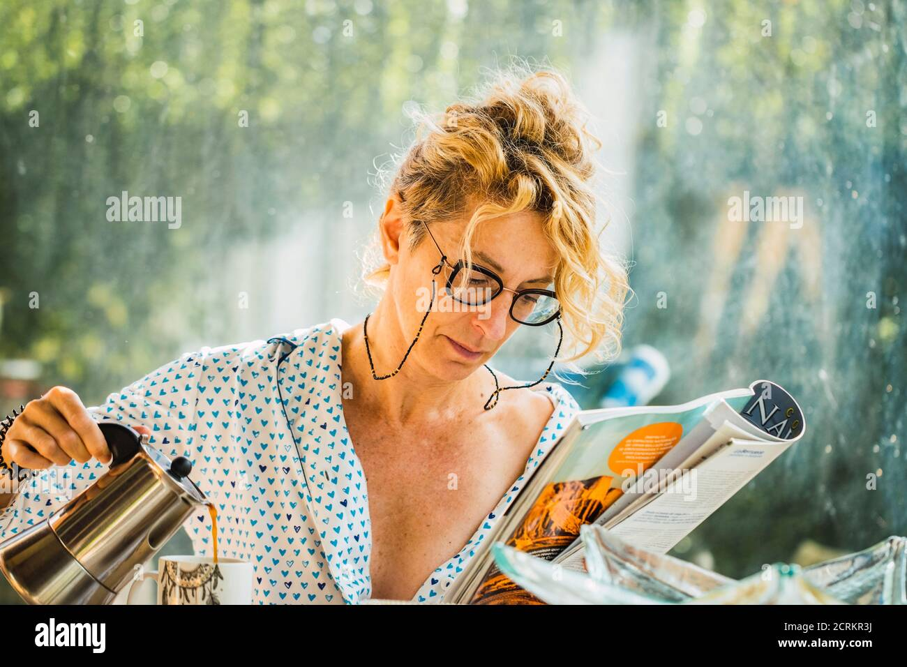 Blonde young mature woman with glasses in pyjamas at home in breakfast time, reading a magazine and preparing a cup of coffee. Stock Photo