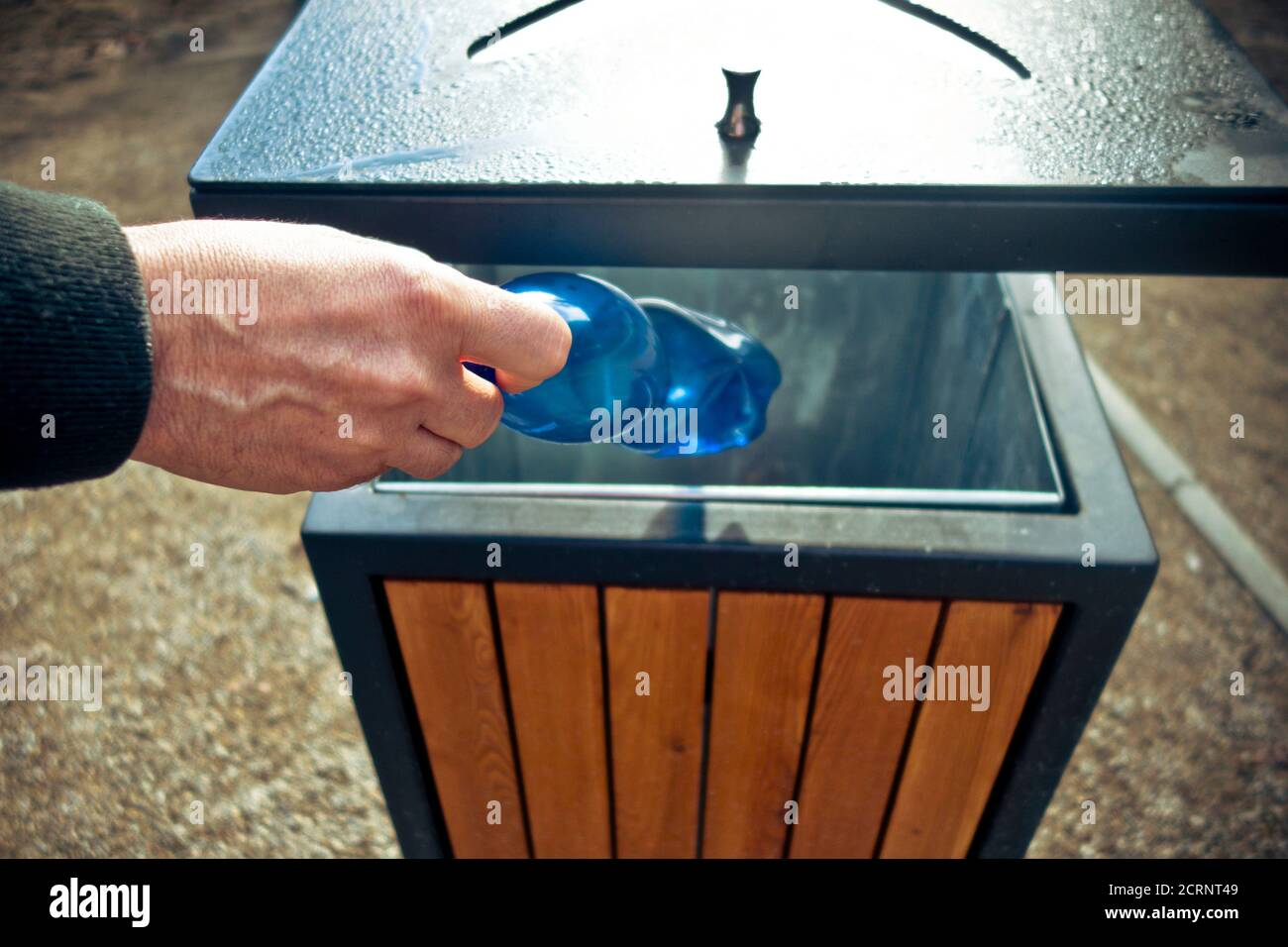 hand putting a plastic bottle into a public waste container Stock Photo