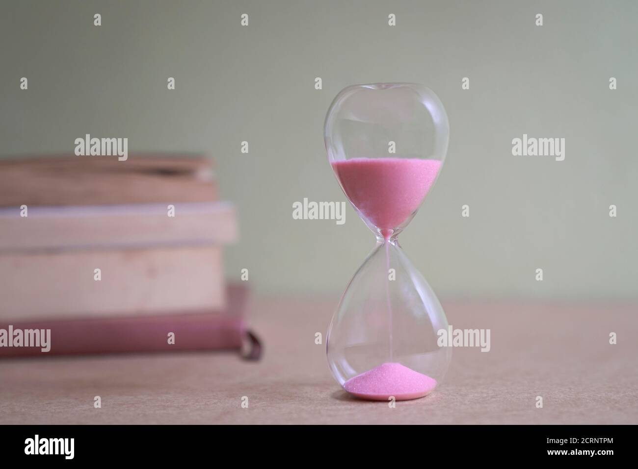 Hourglass with sand flowing with books by the side. Examination, deadlines or student life concept. Stock Photo