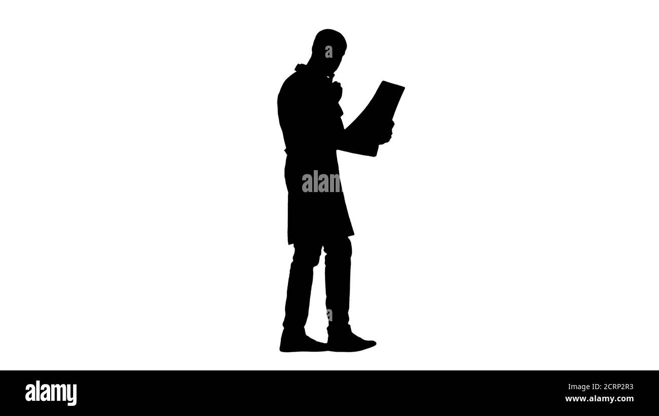 Silhouette Young male physician reading and reviewing a MRI brain scan while walking. Stock Photo