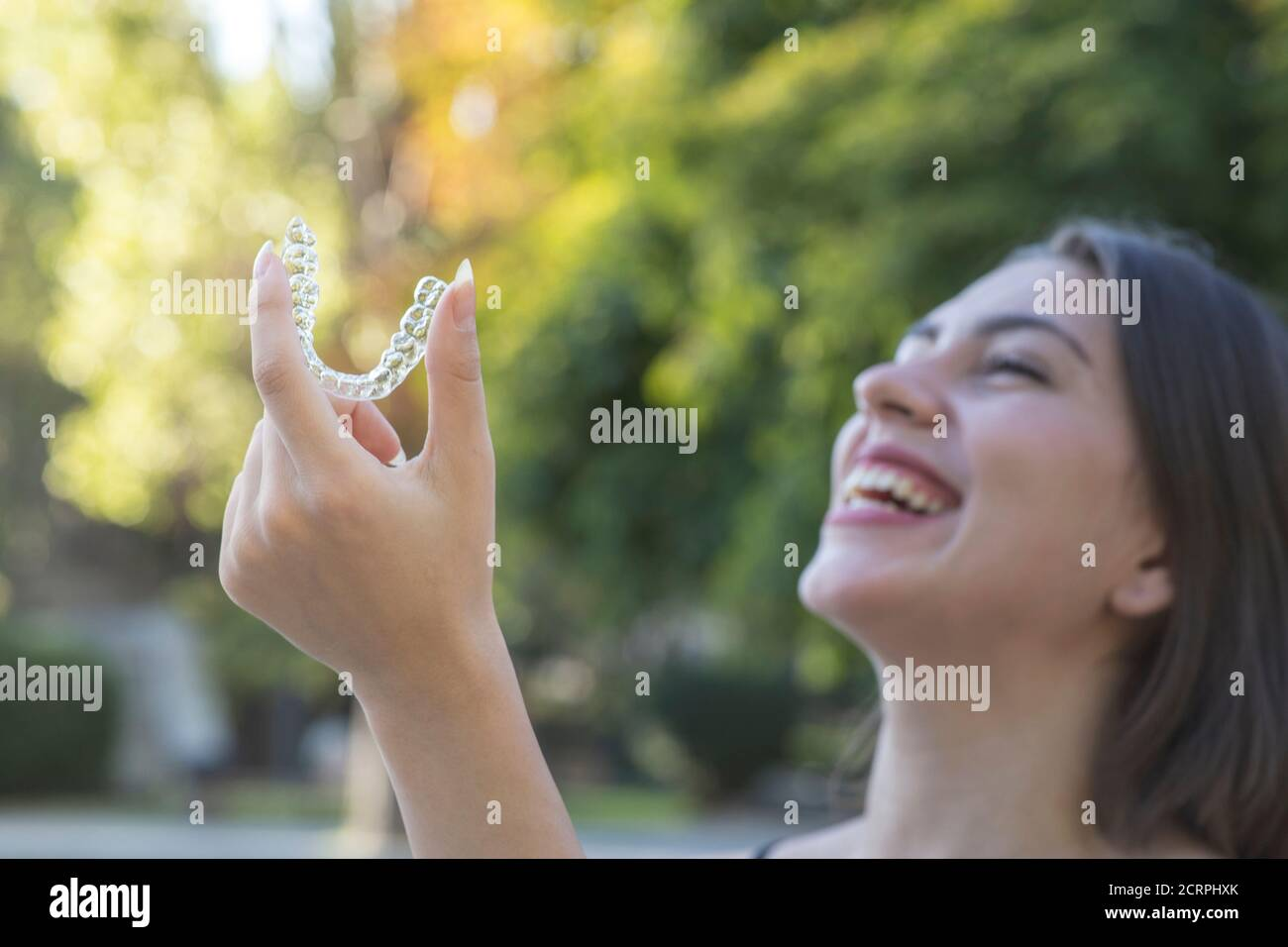 Beautiful smiling Turkish woman is holding an invisalign bracer Stock Photo