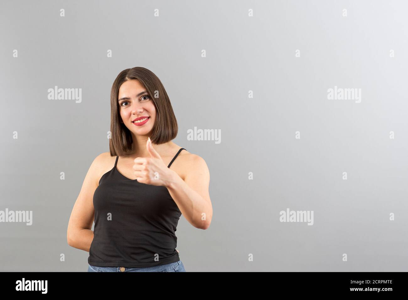 Beautiful Turkish woman is gesturing thumbs up in a studio, isolated shot with copy space Stock Photo