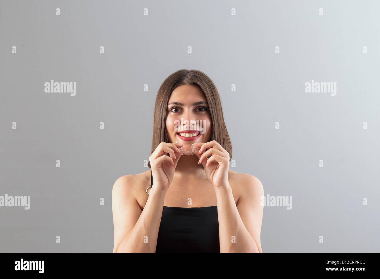 Beautiful smiling Turkish woman is holding an invisalign bracer, Isolated studio shot with copy space Stock Photo
