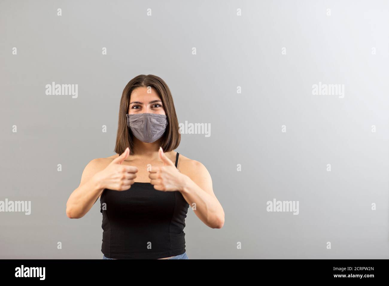 Attractive Turkish woman portrait in positive mood. She is wearing a protecive mask for new normal concept and gesturing thumbs up. Stock Photo