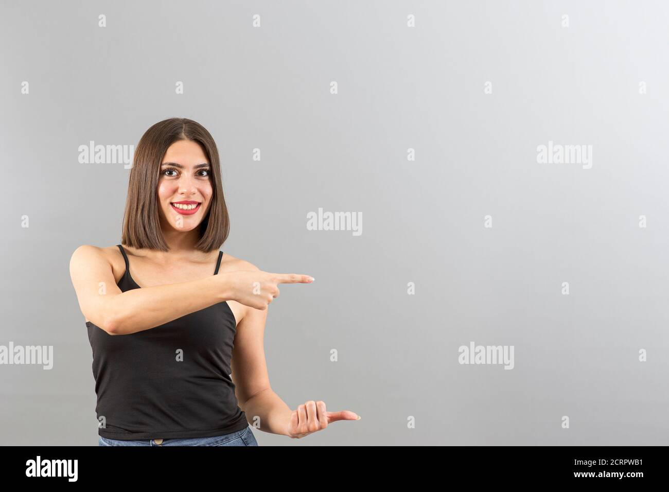 Beautiful Turkish woman with casual clothes is pointing the right side, isolated studio shot with copy space Stock Photo