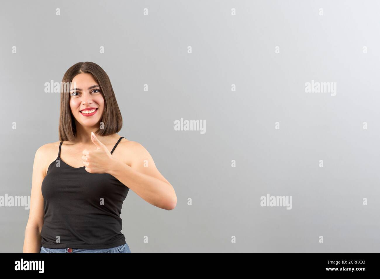 Attractive Turkish woman portrait in positive mood. She is gesturing thumbs up. Stock Photo