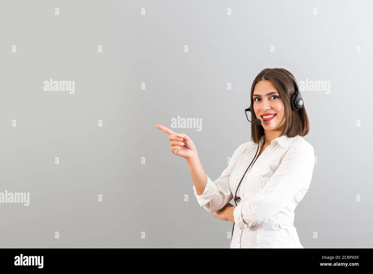 Beautiful Turkish woman with head phone in a studio, isolated shot with copy space, she is pointing the right side Stock Photo