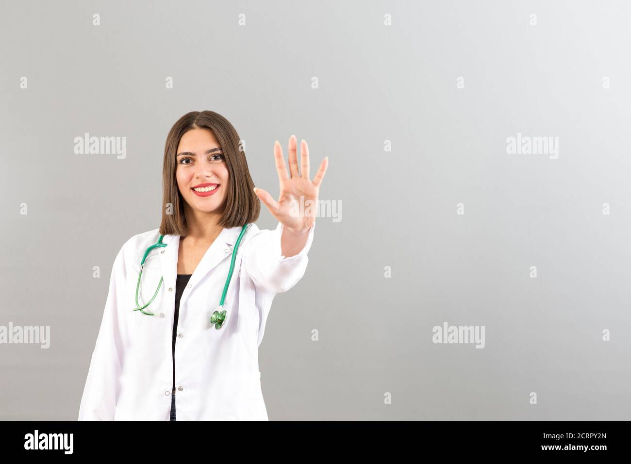 Beautiful smiling Turkish woman doctor portrait in studio she is confident mood, she is gesturing high five Stock Photo