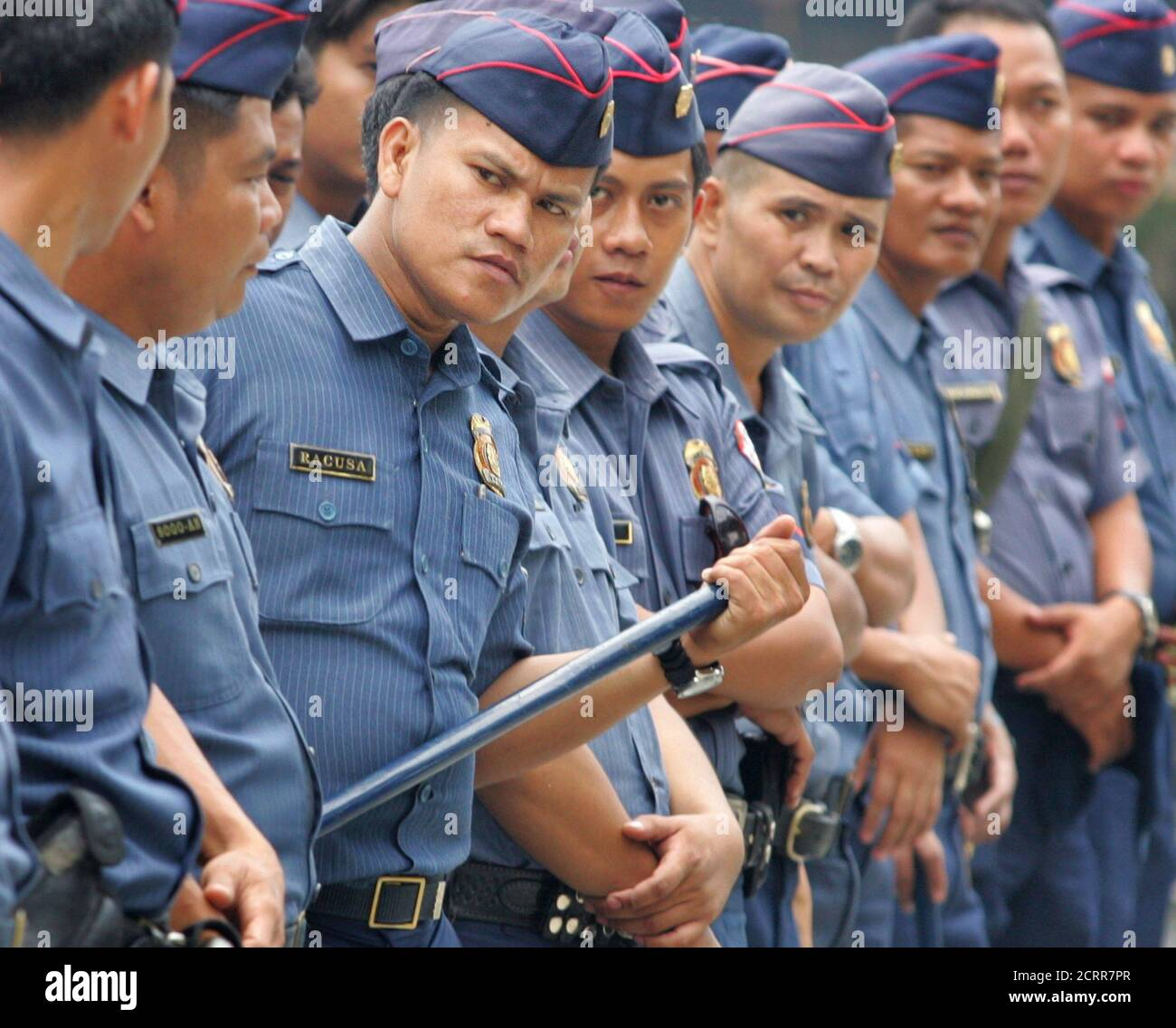 Filipino police monitor an anti-Arroyo march which converged at the EDSA (Epifanio de los Santos Avenue) shrine in Manila July 23, 2005. The shrine is the site of the 1986 and 2000 People Power uprising. President Gloria Macapagal Arroyo, who is facing vote-rigging accusations, is scheduled to give her state-of-the-nation address on July 25. REUTERS/Adrees Latif  AL/CCK Stock Photo