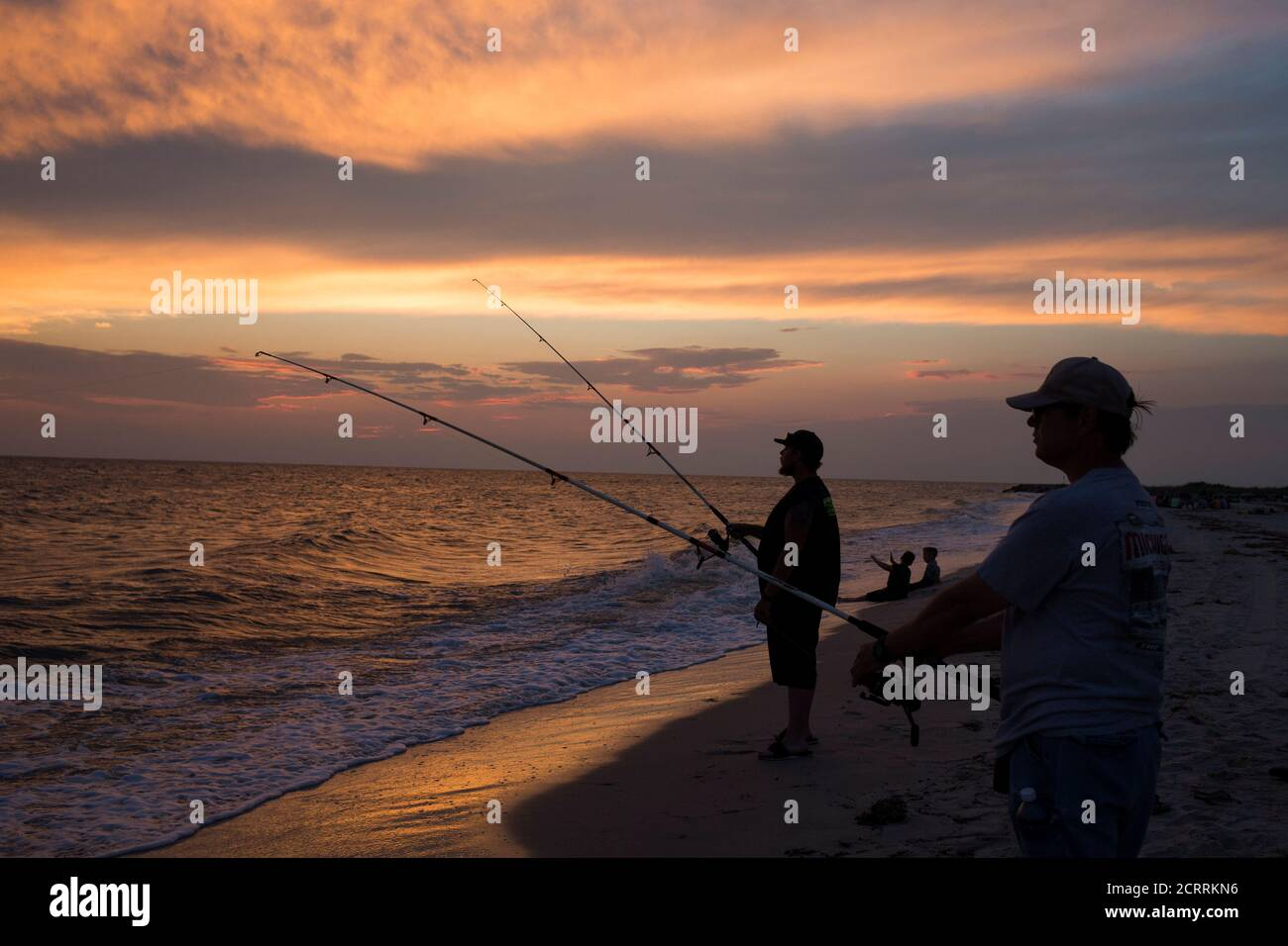 Visitors fish along a beach at sunset on Tangier Island, Virginia, U.S., on August 3, 2017.  REUTERS/Adrees Latif Stock Photo