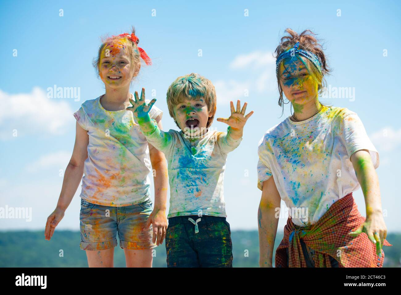 Cheerful kids showing her hands painted in bright colors. Colorful faces, color splash, coloured powder on children body. Stock Photo