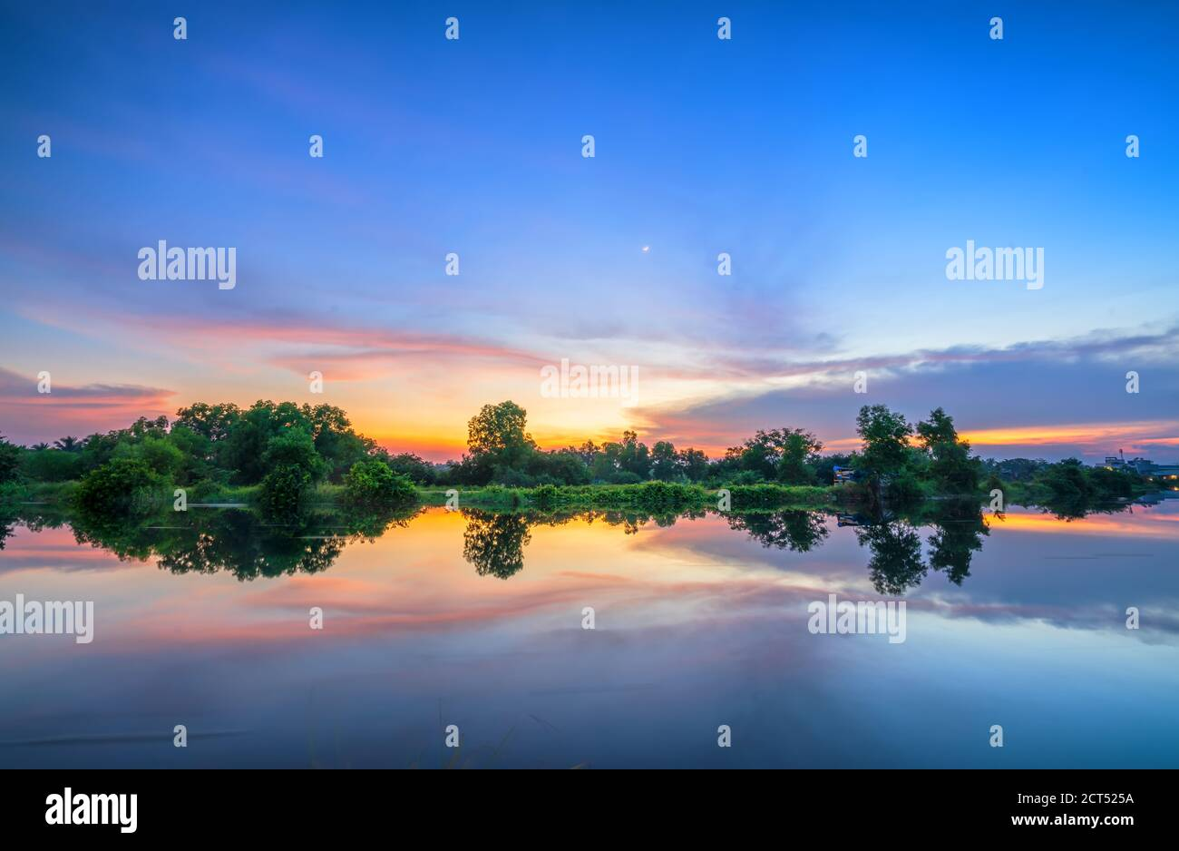 The sunset on the riverbank reflects the peaceful background in the countryside Stock Photo