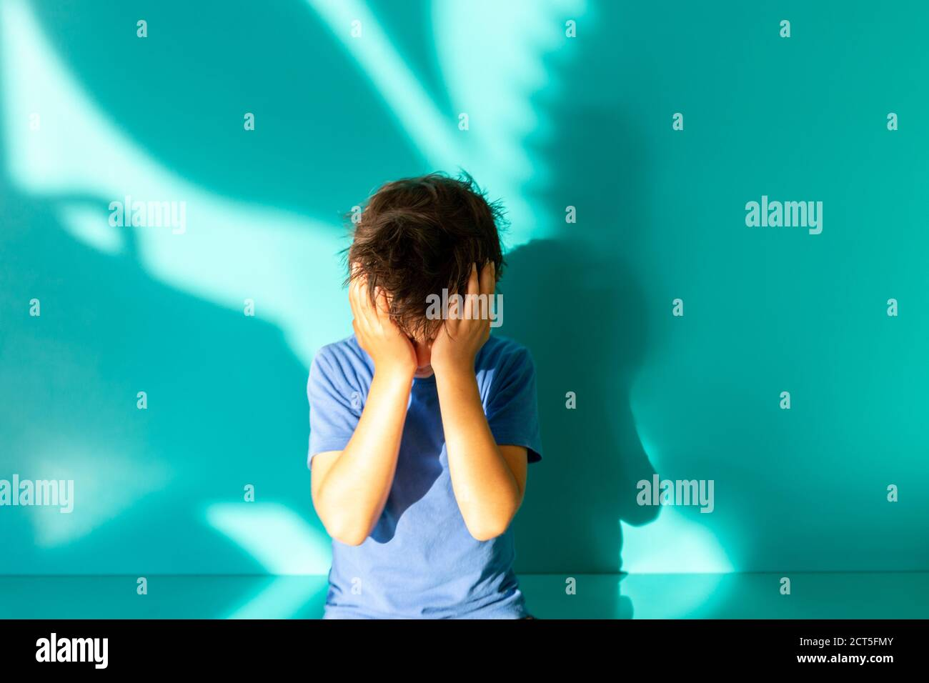 Portrait of a sad or frustrated brunette boy in a blue shirt. thumbs up. turquoise background with shadow. Education. Looking and smiling at the camera Stock Photo