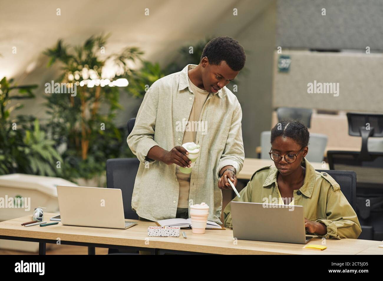 Portrait of two African-American people working in modern open space office, focus on young man instructing colleague and pointing at laptop screen , copy space Stock Photo