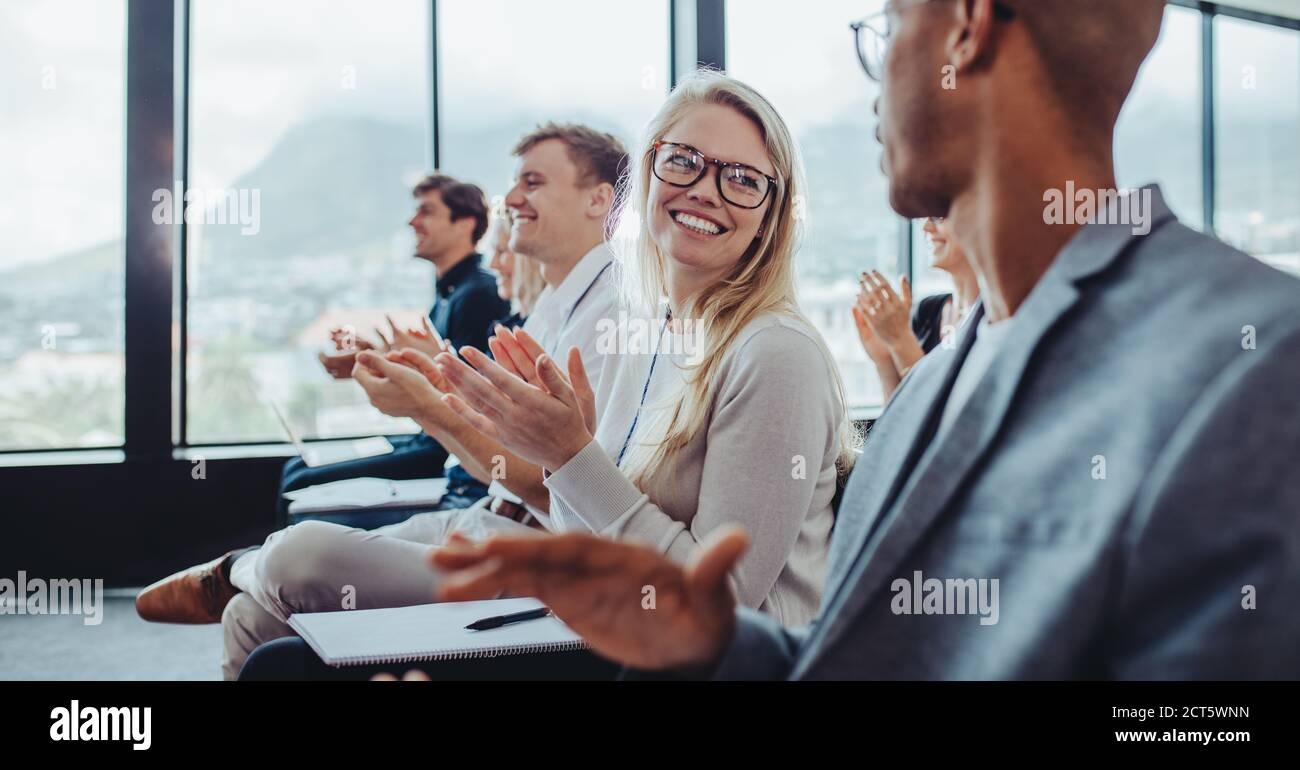 Group of businesspeople applauding speaker after conference presentation. Business men and women sitting in audience clapping hands. Stock Photo
