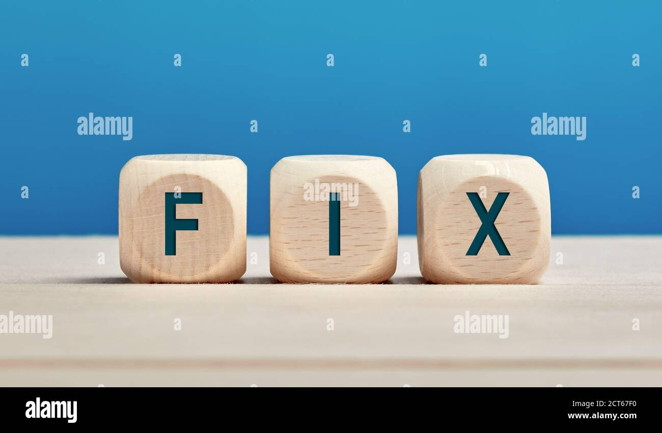 The word fix on wooden cubes against blue background. Fixing, repairing or solution concept. Stock Photo