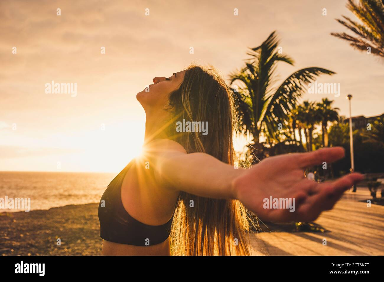 Athlete sporty and beautiful young woman stretch and breathe after workout in outdoor with sunset and sunlight in background with ocean and sky - heal Stock Photo