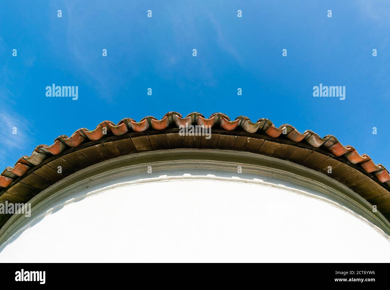 View from below of the edge of a circular tile roof over blue sky Stock Photo