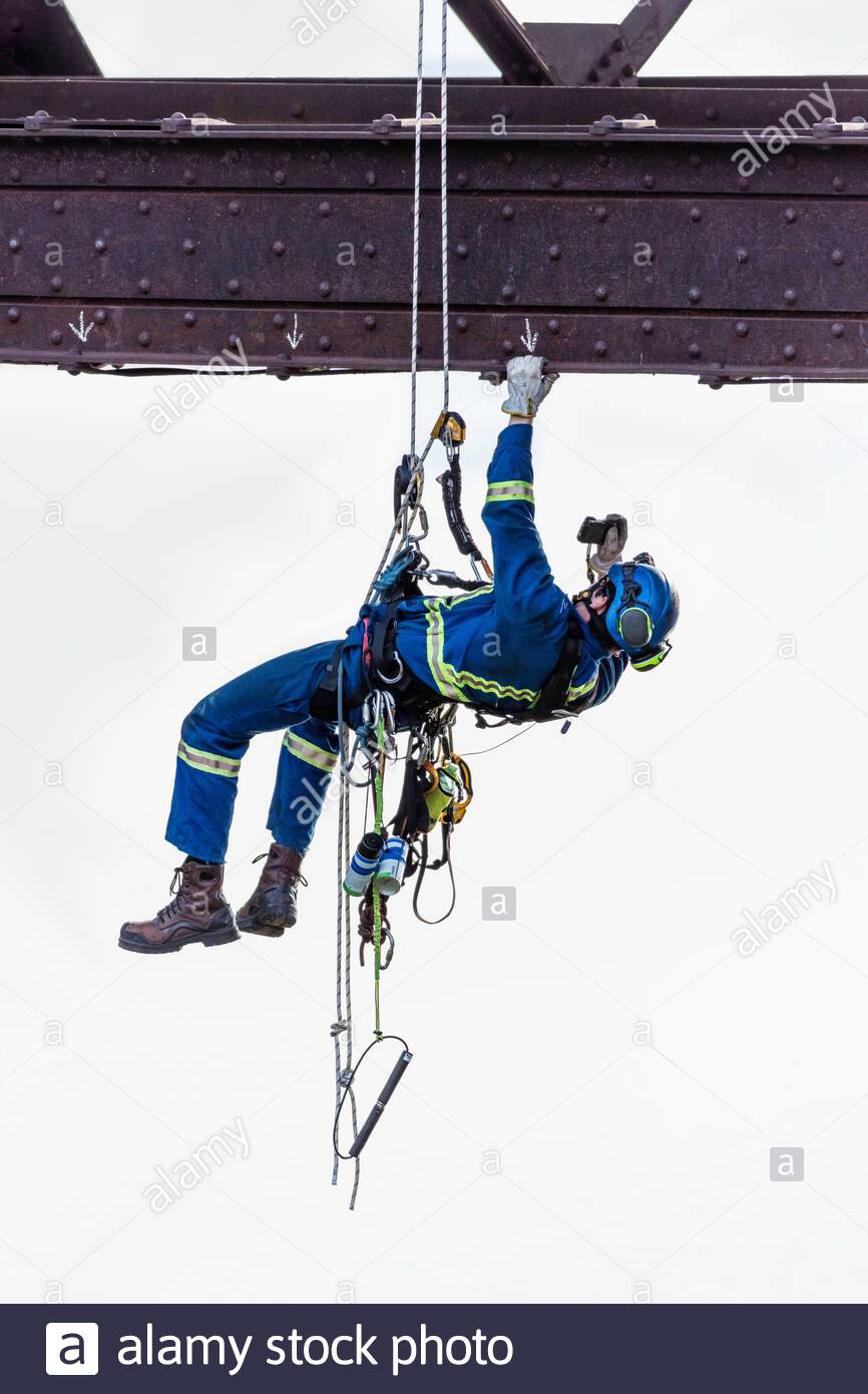 Steeplejack industrial climber using rope access to inspect bridge maintenance repair Toronto Ontario Canada Stock Photo