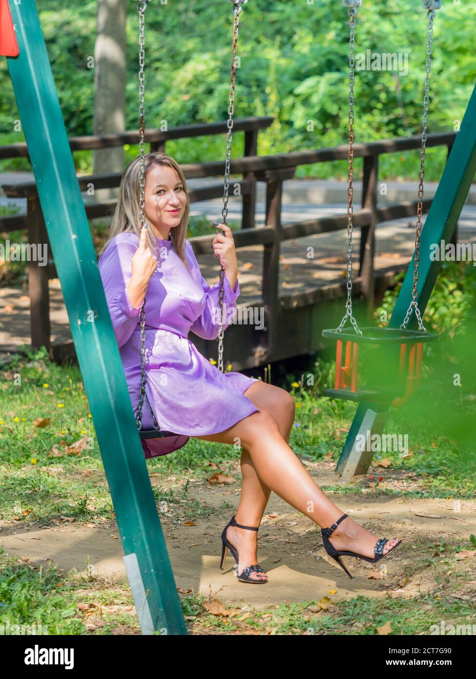 Playful on swings in childfrens playground park before small wooden footbridge foot-bridge eyeshot eyes eye contact looking at camera Stock Photo