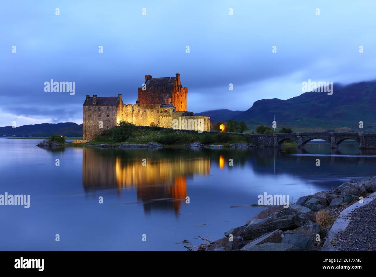 Eileen Donan Castle floodlit after sunset on a cloudy evening, West Highlands, Scotland, UK Stock Photo