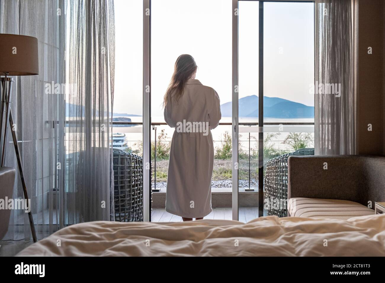 Beautiful woman from back in bathrobe standing on terrace of hotel room with Sea View morning sunrise Stock Photo