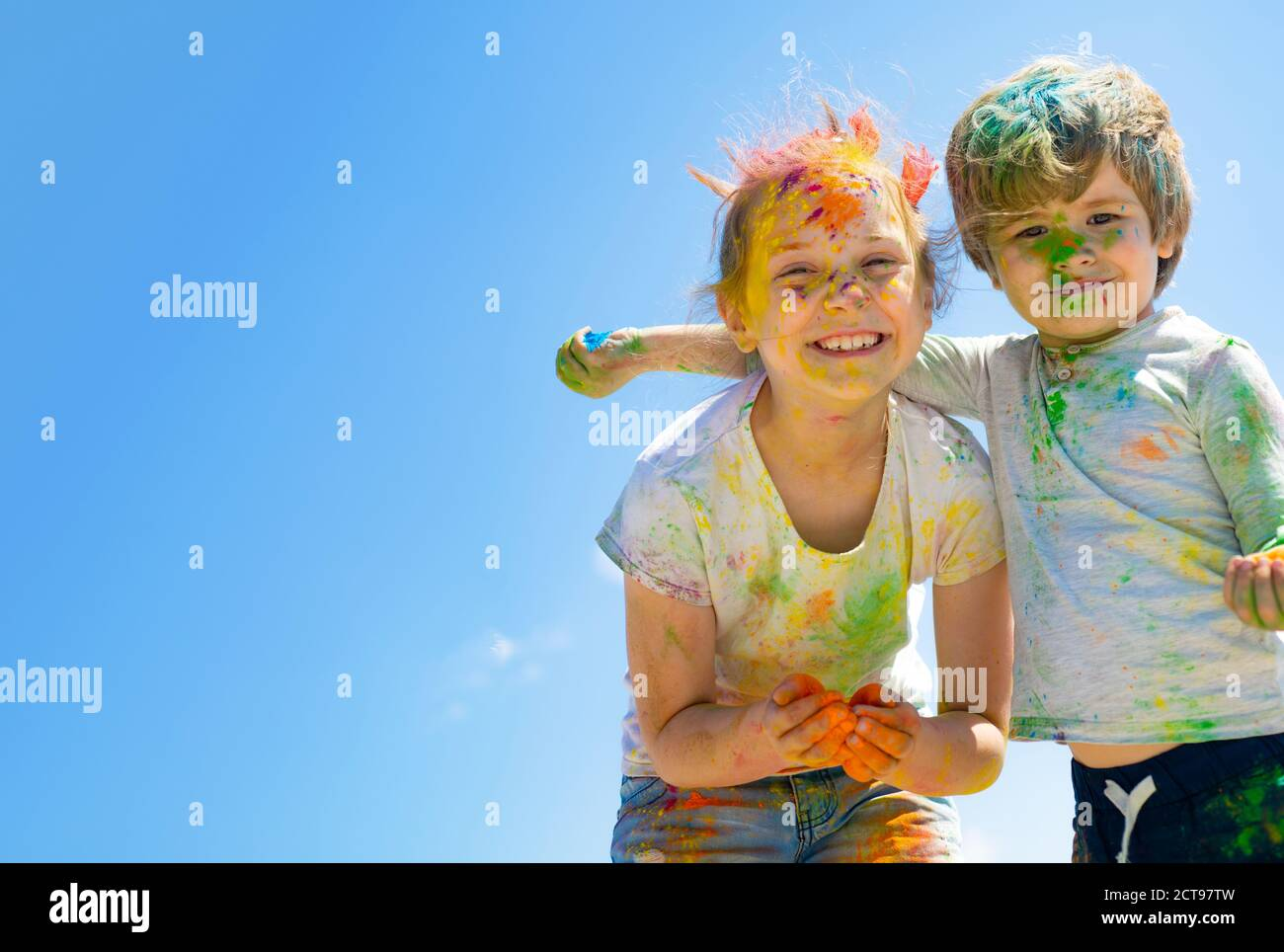 Two kids with face smeared with colors Stock Photo