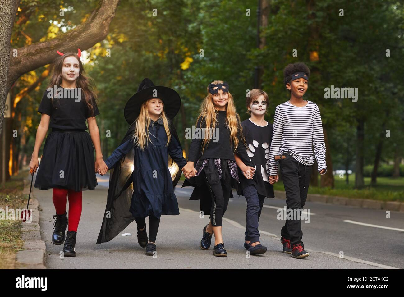 Full length portrait of multi-ethnic group of kids walking in street while trick or treating on Halloween Stock Photo