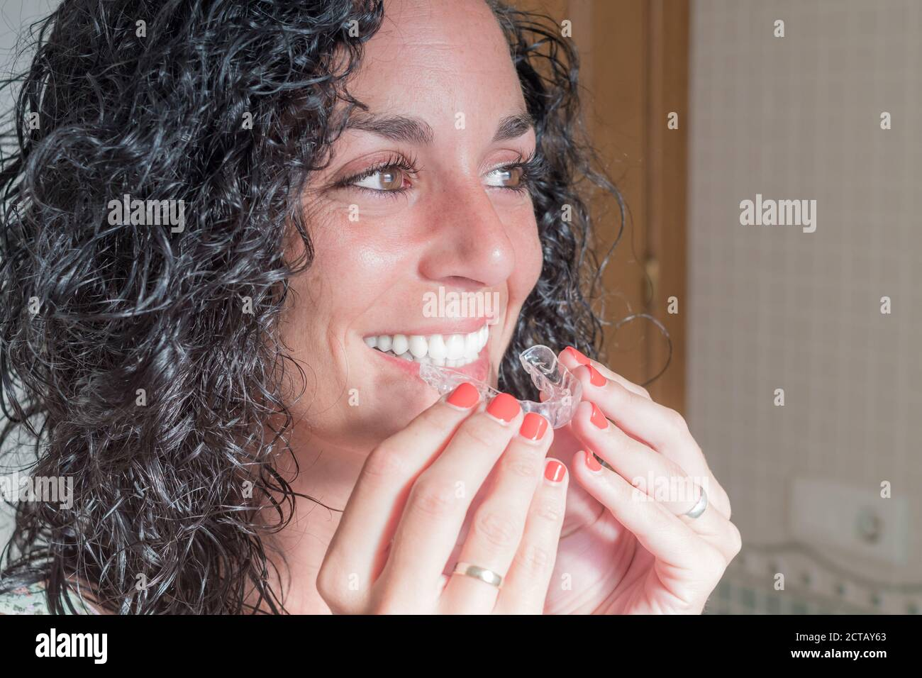Close-up of young curly haired brunette woman putting on her invisible silicone aligner. dental correction. mobile orthodontics Stock Photo