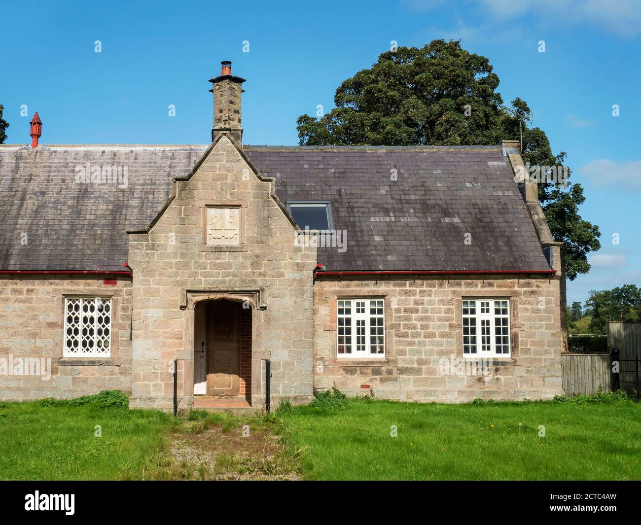 Former village school building which houses the village hall in the left hand side Little Ribston near Knaresborough North Yorkshire England Stock Photo
