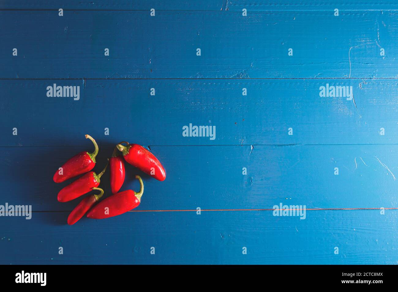 Minimal flat lay view of chili peppers in a row over blue vintage backdrop with copy space Stock Photo