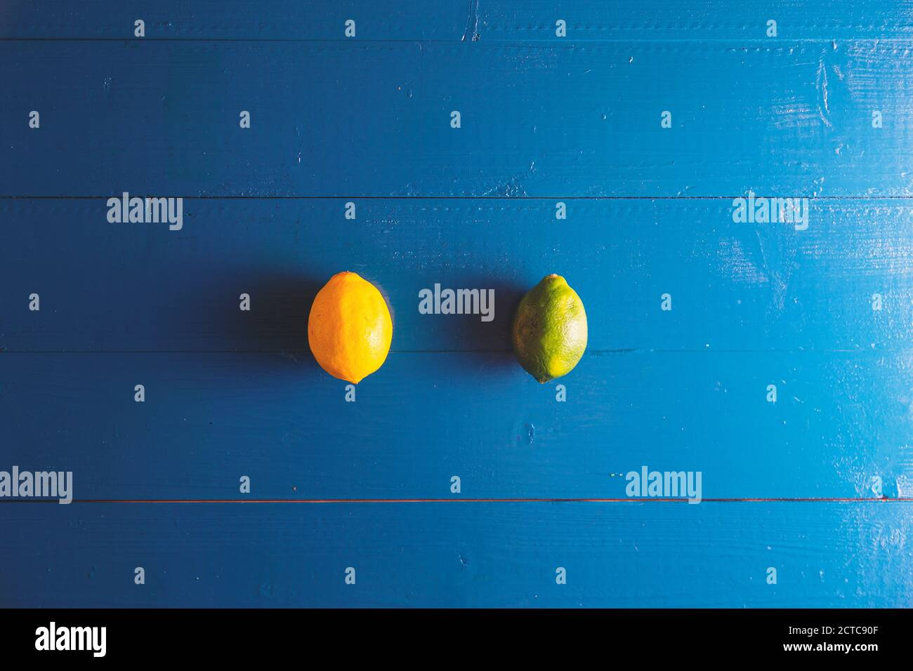 Minimal flat lay view of lime, lemon over blue vintage backdrop with copy space Stock Photo