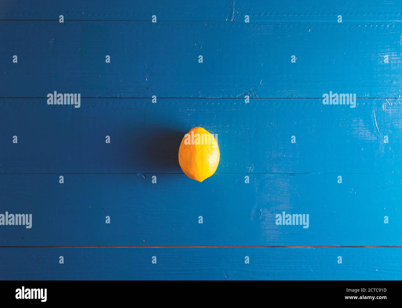 Minimal flat lay view of lemon over blue vintage backdrop with copy space Stock Photo