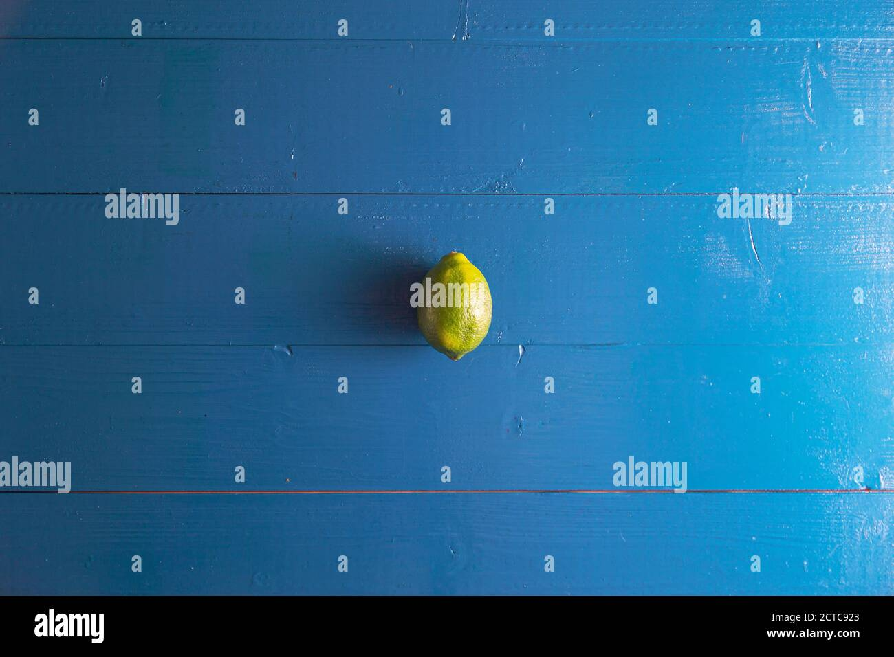Minimal flat lay view of lime over blue vintage backdrop with copy space Stock Photo