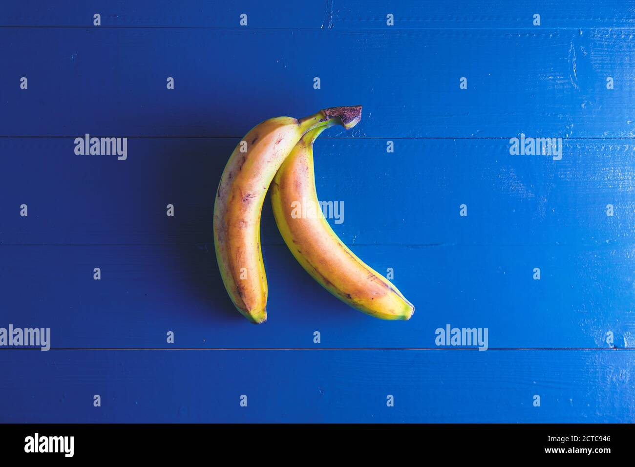 Minimal flat lay view of banan over blue vintage backdrop with copy space Stock Photo