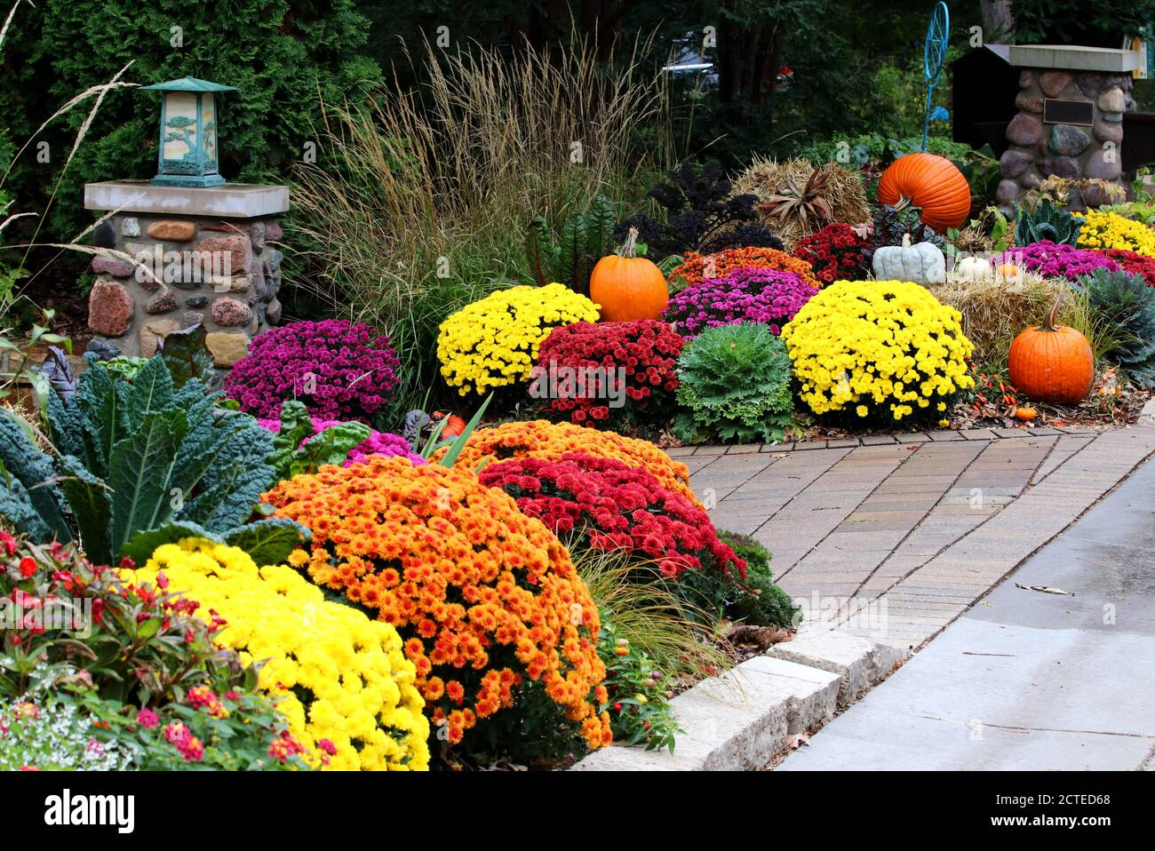 Colors of autumn background. Bright colors fall season outdoor decoration with potted chrysanthemums and unusual pumpkins on the hay bricks as a part Stock Photo