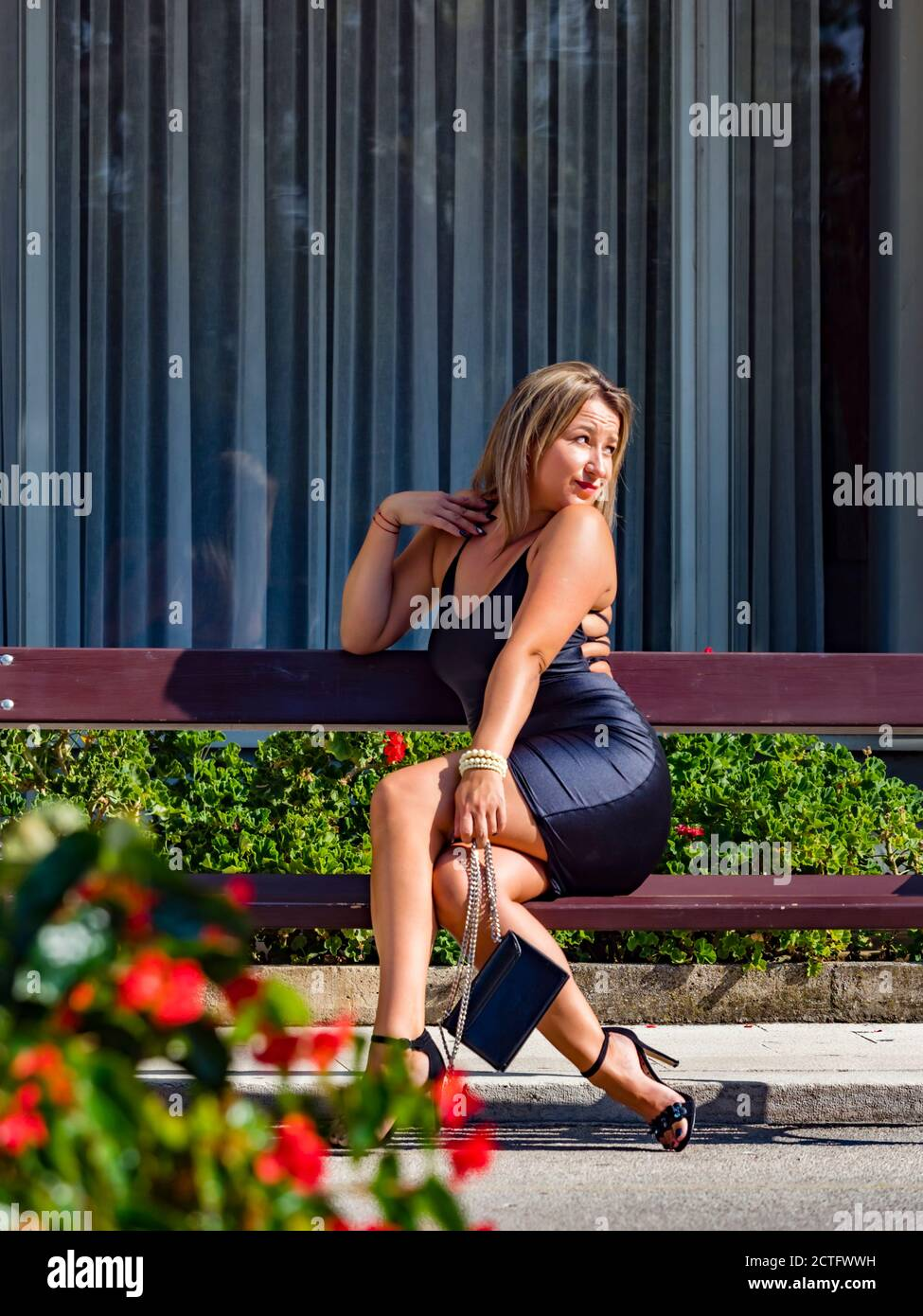 Young woman is sitting on wooden bench expecting for someone waiting wait looking away hoping hope aside hand hold holding purse legs heels Stock Photo