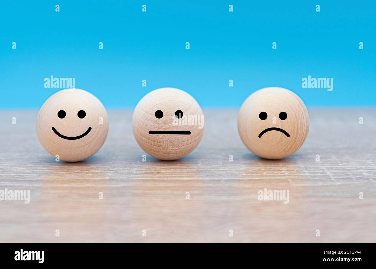 Three wooden faces with emotions: smile - happy, serious - neutral and angry - displeased, concept picture Stock Photo