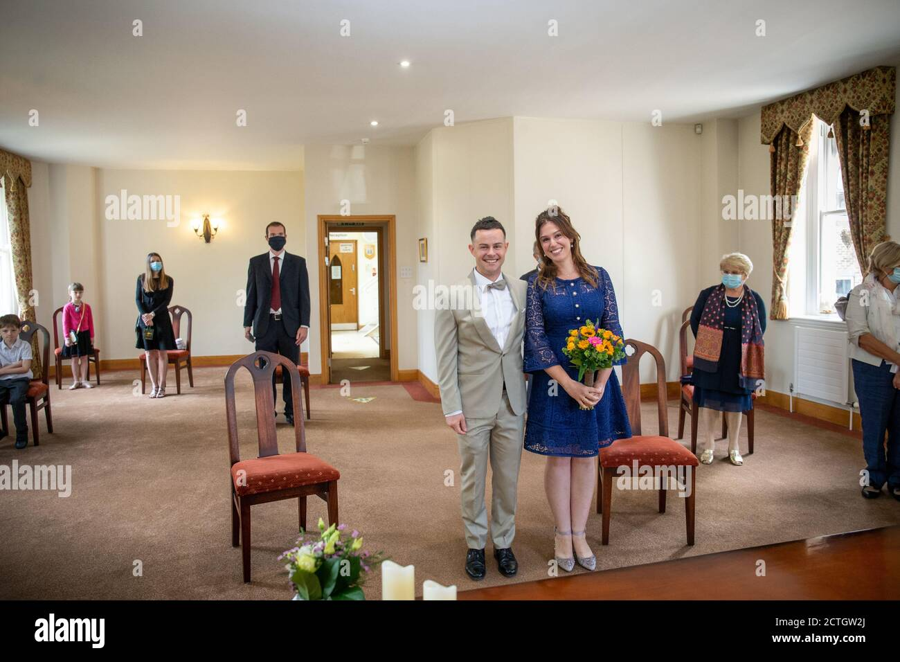 Couple getting married at St Albans Register Office during Coronavirus / Covid-19 pandemic 2020. With guests wearing face masks and face coverings Stock Photo