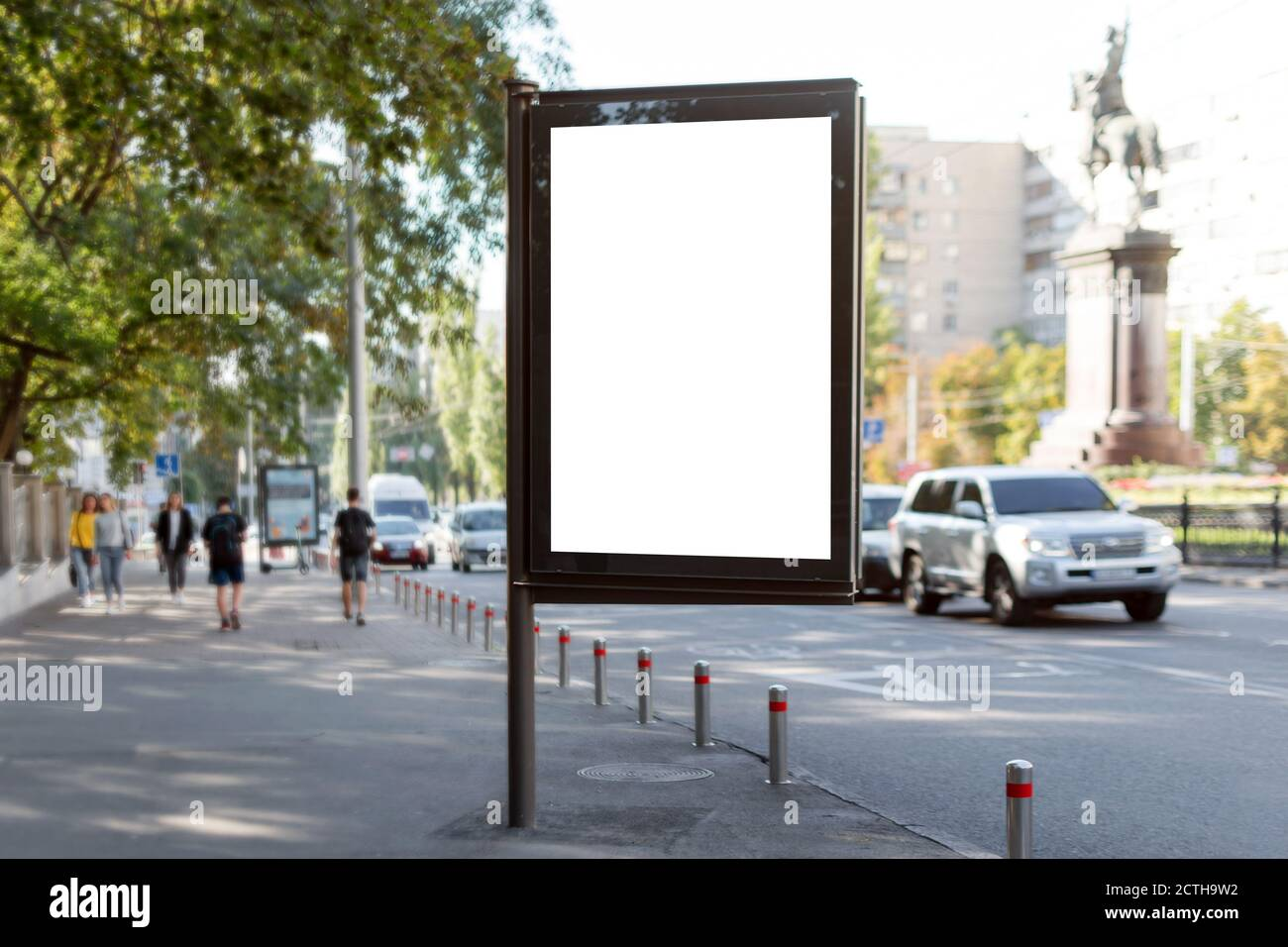 Blank mock up of vertical street poster billboard on city background. Blanck billboard for advertising on the sidewalk next to the road. Stock Photo