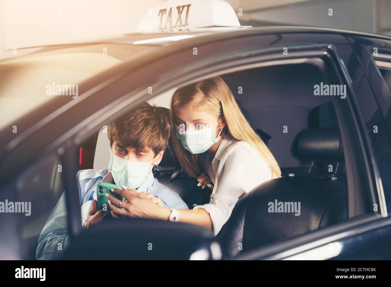 New normal. Teenager sitting in the back of a car with a mask. Young woman in a taxi protected by a mask. Road safety. Coronavirus pandemic. use smart Stock Photo