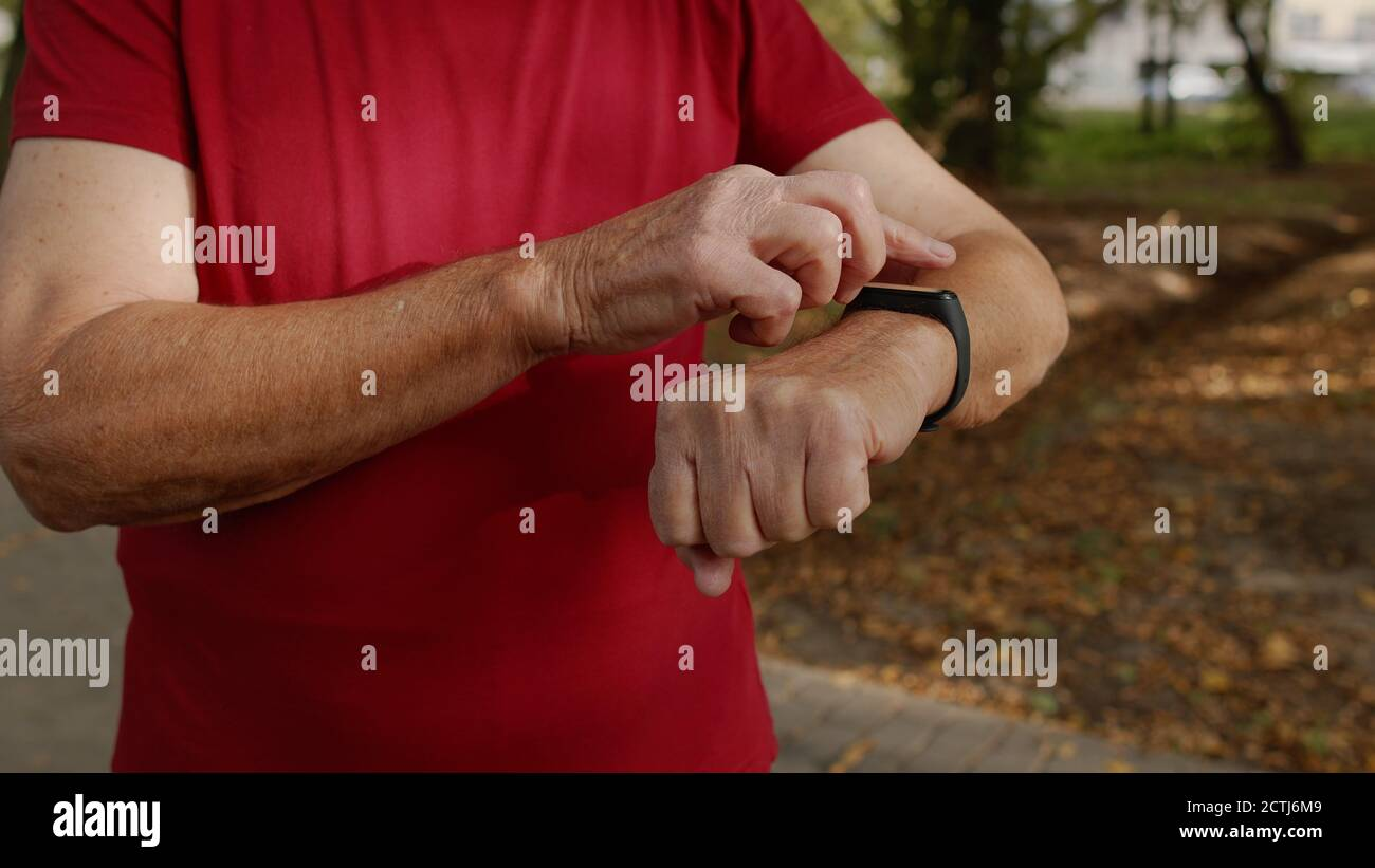 Senior old runner man starting tapping touchscreen on smart watch, tracking distance, checking pulse during fitness workout. Heart rate monitor before jogging. Healthy lifestyle concept Stock Photo