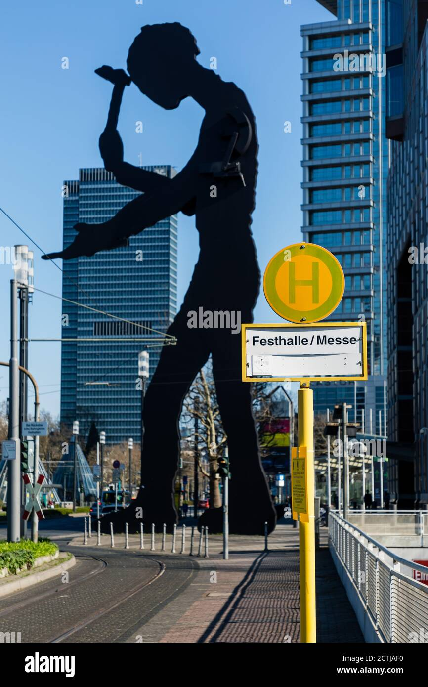 """Frankfurt, Hesse, Germany: Sign of Tram Station """"Festhalle/Messe"""" in front of the monumental kinetic sculpture """"Hammering Man"""" by Jonathan Borofsky. Stock Photo"""