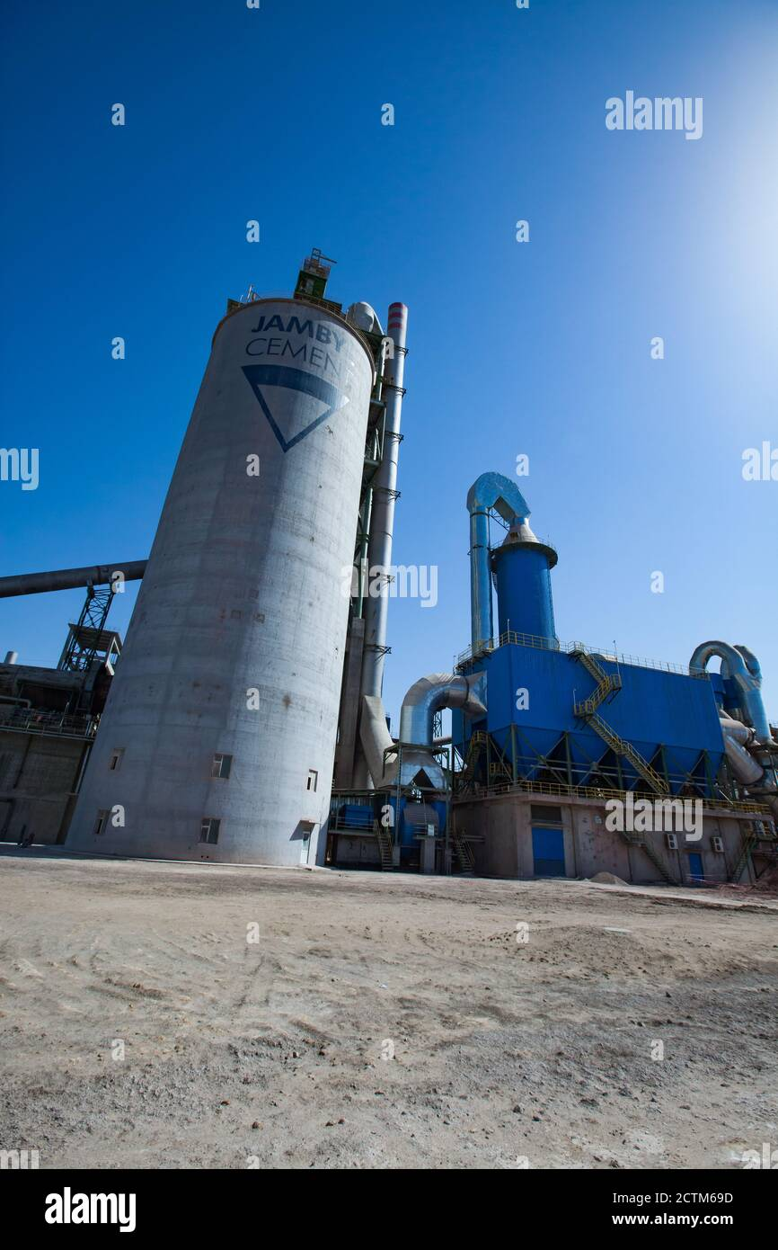 Mynaral/Kazakhstan - April 23 2012: Jambyl Cement plant industrial buildings and silos with bright sun. Wide-angle view. Stock Photo