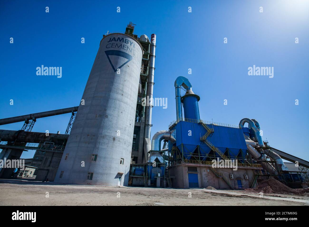 Mynaral/Kazakhstan - April 23 2012: Jambyl Cement plant. Industrial buildings and silos. Panorama view. Clear blue sky with sun. Stock Photo