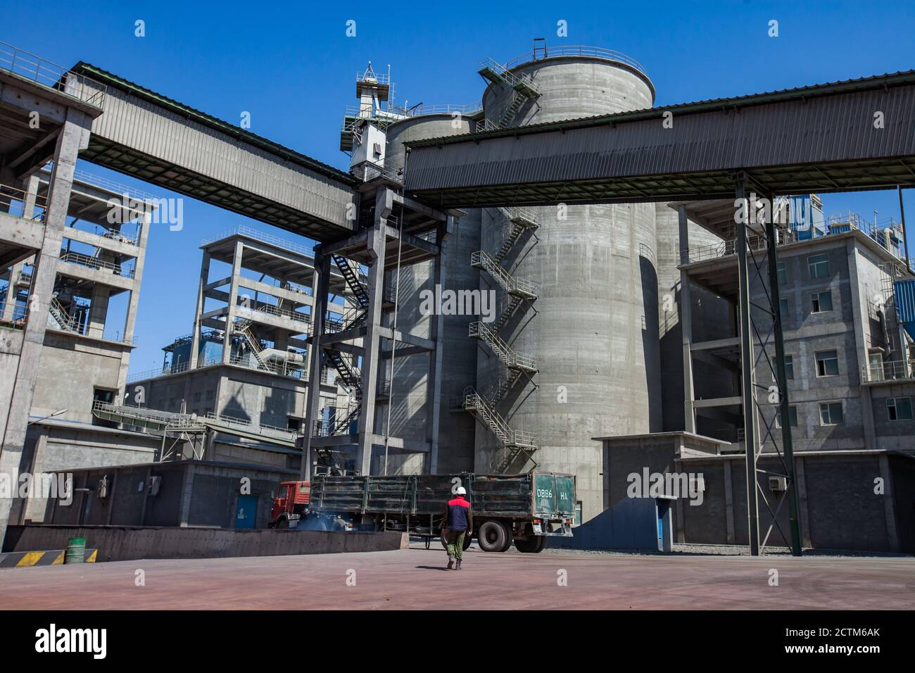 Mynaral/Kazakhstan - April 23 2012: Modern Jambyl Cement plant. Industrial buildings, cement silos, truck and worker on blue sky. Stock Photo
