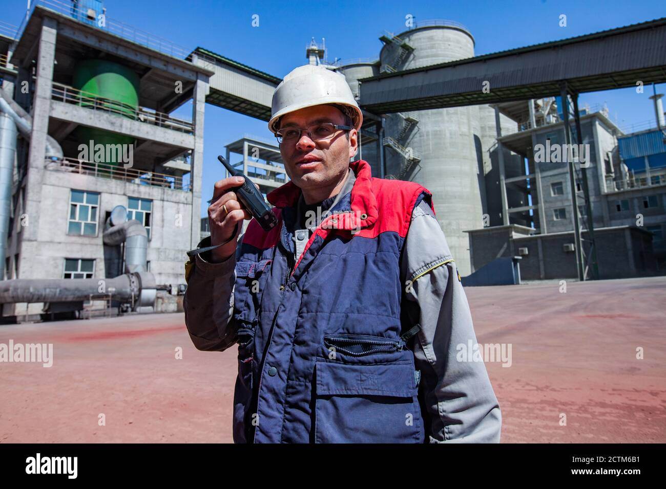 Engineer or worker in white helmet and glasses speaking walkie-talkie. On blurred grey Jambyl Cement plant silos and industrial buildings background. Stock Photo