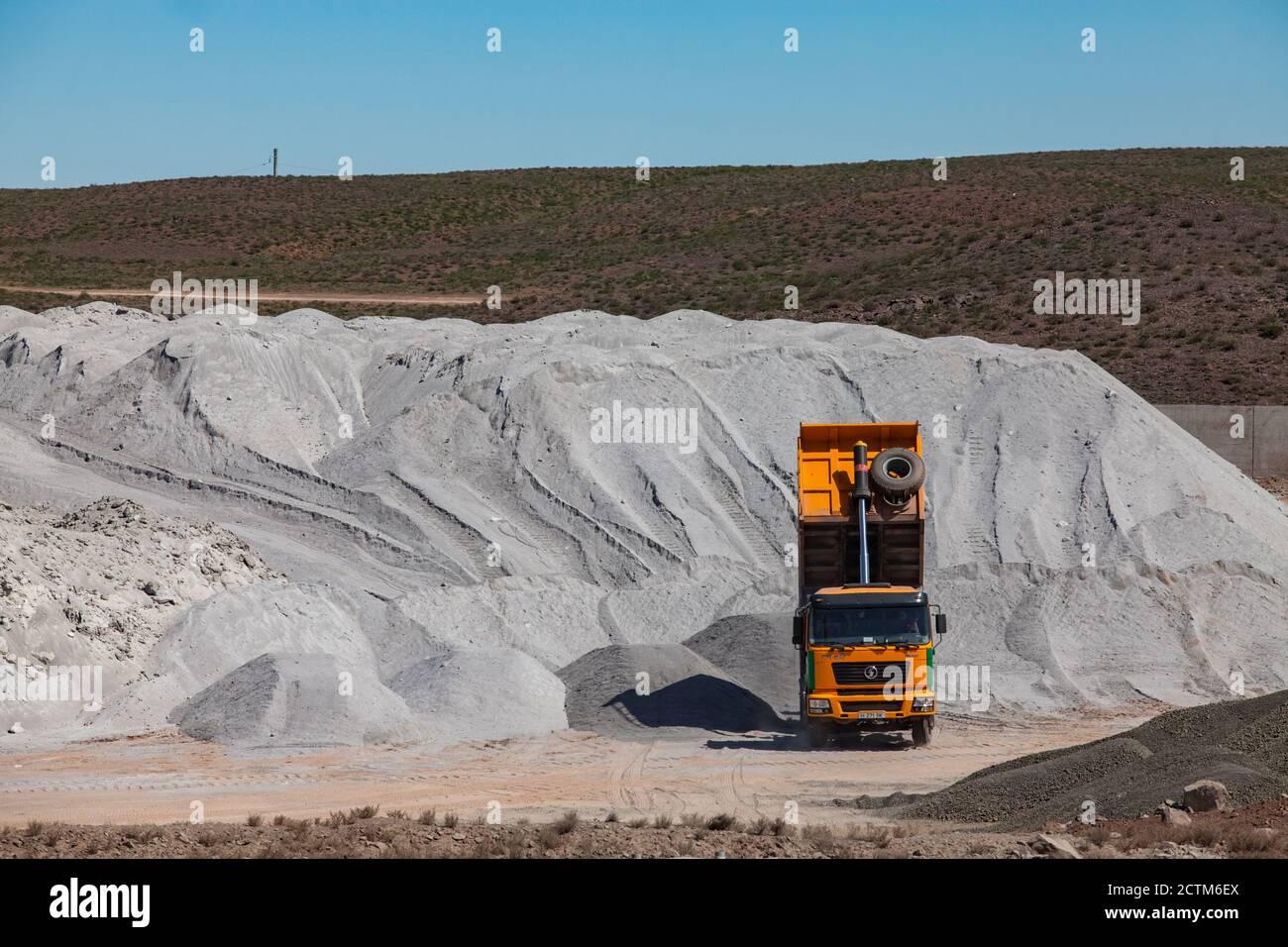 Mynaral/Kazakhstan - April 23 2012: Jambyl Cement plant storage of raw materials. Heap of clinker Minerals and yellow dump truck. Stock Photo